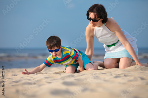 Young mather and son playing on the beach