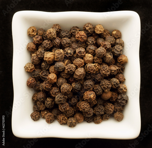 Spice black pepper peas in a ceramic bowl. Isolated on black.
