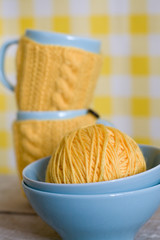 Two blue cups in yellow sweater on a fabric background