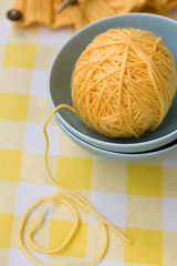 Yellow ball of yarn for knitting in blue plate and pattern