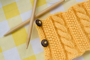 Yellow knitted pattern on a fabric background