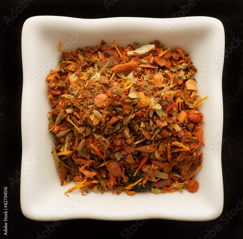 Spice for pilaf in a ceramic bowl. Isolated on black.