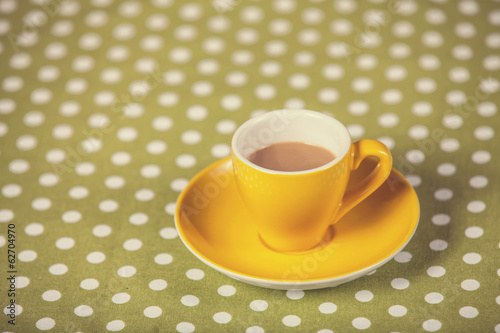 Cup of a coffe on polka dot cover.