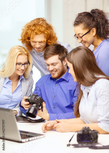 smiling team with laptop and photocamera in office