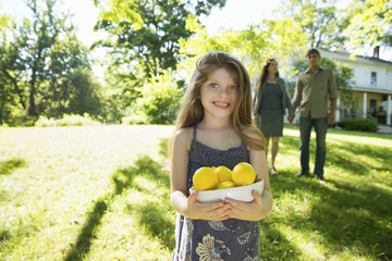 Farm. Children And Adults Working Together. A Girl Holding A Crate Of Lemons, Fresh Fruits. Two Adults In The Background.