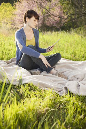 A Young Woman Sitting In A Field, On A Blanket, Holding And Looking At The Screen Of A Digital Tablet. Working Outdoors.