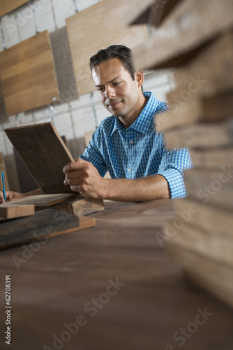 A Young Man In A Workshop. Examing A Wood Sample And Taking Notes On Paper.