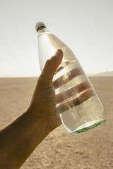 The Landscape Of The Black Rock Desert In Nevada. A Man'S Hand Holding A Bottle Of Water. Filtered Mineral Water.