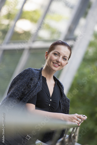 Business People. A Woman In A Grey Jacket With Her Hair Up, Leaning On A Railing.