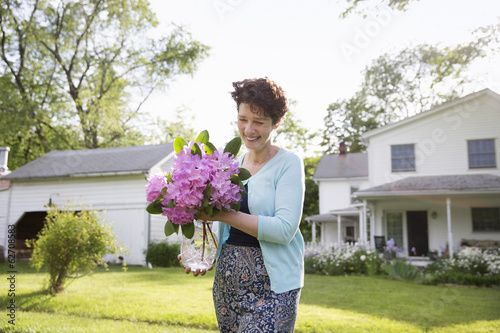 Family Party. A Woman Carrying A Large Bunch Of Rhododendron Flowers, Smiling Broadly.