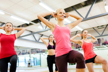 group of smiling femalewith trainer exercising
