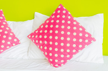 Colorful polka pillow on white bed
