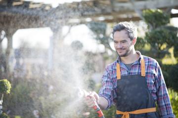 gardener watering potted trees in a garden center