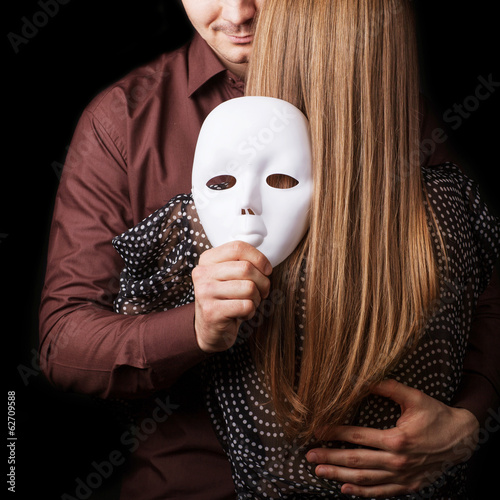 Fashion man holding a white mask face. Psychological concept.