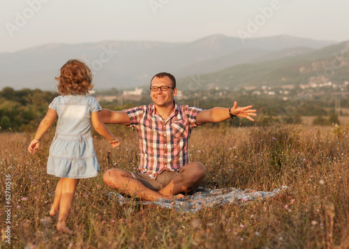 father and daughter on the field in the mountains happy