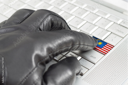 Hacking Malaysia concept with hand wearing black leather glove p