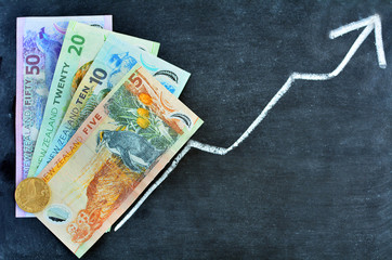 NZ Dollar banknotes with upward trend arrow