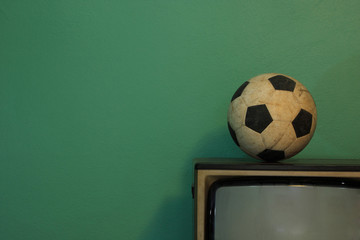 An old soccer ball on a retro TV with retro green paint wall