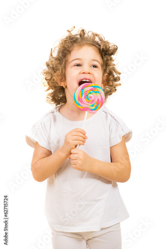 Happy little girl licking a large lollipop