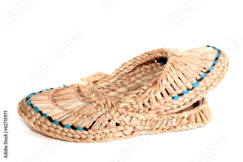 Old Russian sandals made of bark on the white background