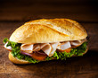 Crusty roll with sliced ham and salad ingredients