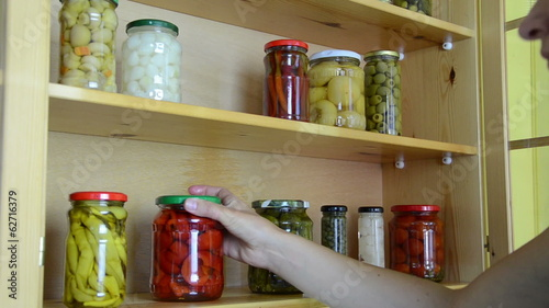 housewife puts on the shelves canned marinated vegetables  jars