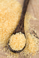 brown cane sugar in a wooden spoon