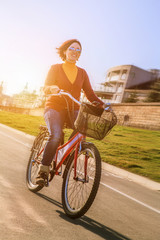 Happy young woman ride by bicycle