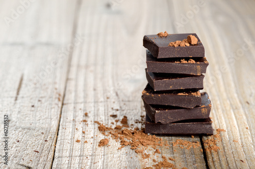 Staande foto Snoepjes Pile of chocolate pieces with cocoa on wooden background