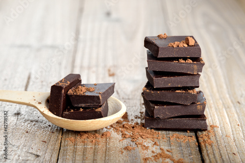 Fototapeta Chocolate pieces with cocoa in wooden spoon