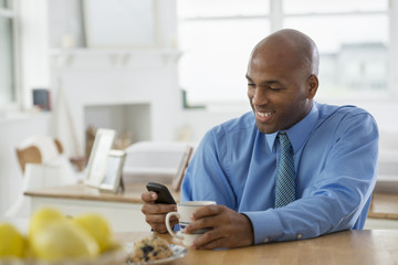 A Man In A Blue Shirt, Sitting At A Breakfast Bar Using A Smart Phone.