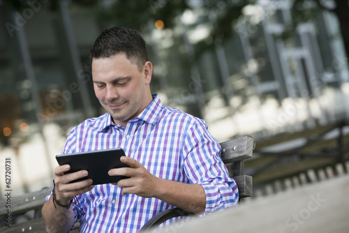 Summer In The City. A Man Sitting On A Bench Using A Digital Tablet.