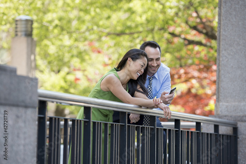 A Couple, Man And Woman Checking A Smart Phone, Under The Shade Of Trees In The Park.