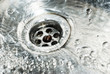 Stainless steel sink plug hole close up with water - 62721104