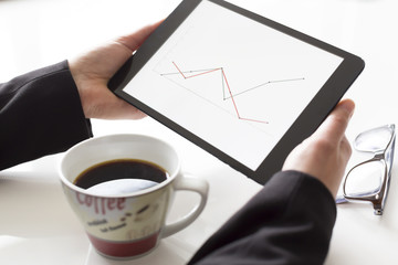 Hands with tablet analyzing diagram