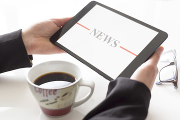 Hands with tablet reading news