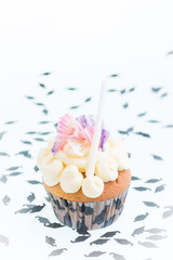 Graduation cupcake with mortarboard confetti background