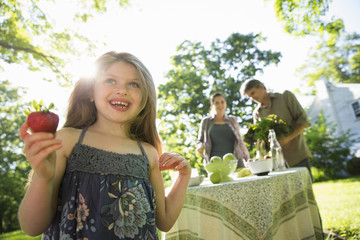 On The Farm. Children And Adults Together. A Young Girl Holding A Large Fresh Organically Produced Strawberry Fruit. Two Adults Beside A Round Table.