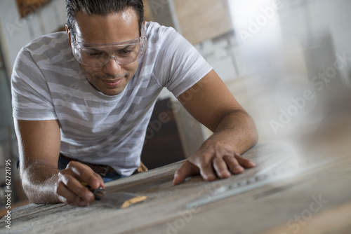 A Young Man In A Workshop Measuring And Drawing Out Plans On A Counter Top.