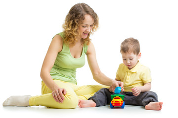 kid boy and mother playing together with toy