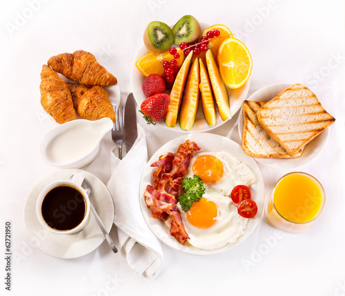 Breakfast with fried eggs, coffee,  juice, croissant and fruits
