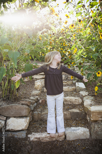 A Child Standing On A Garden Path, With A Background Of Sunflowers.
