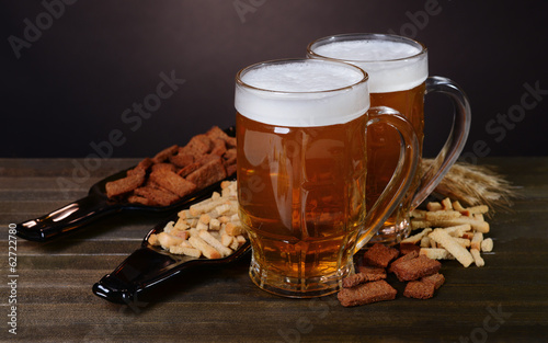 Glasses of beer with snack on table on dark background