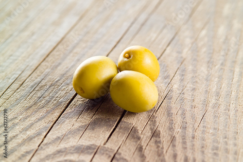 Three green olives on wooden table