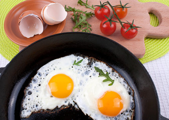 Two fried eggs sunny side up in a cast iron skillet