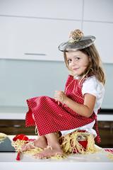 Deutschland, Mädchen mit Spaghetti auf Küchenarbeitsplatte spielen