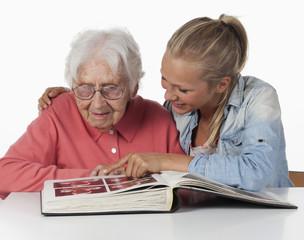 Seniorin und Teenager- Mädchen, Foto-Album anschauen