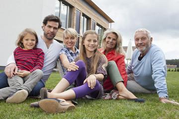 Deutschland, Nürnberg, Familie sitzt vor dem Haus