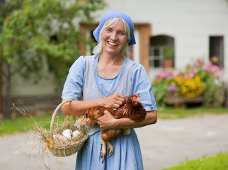 Deutschland, Bayern, Seniorin mit Korb mit frischen Eiern und Hühnerfleisch