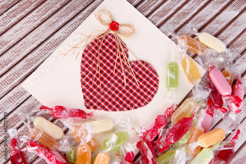 Tasty candies with card on wooden background